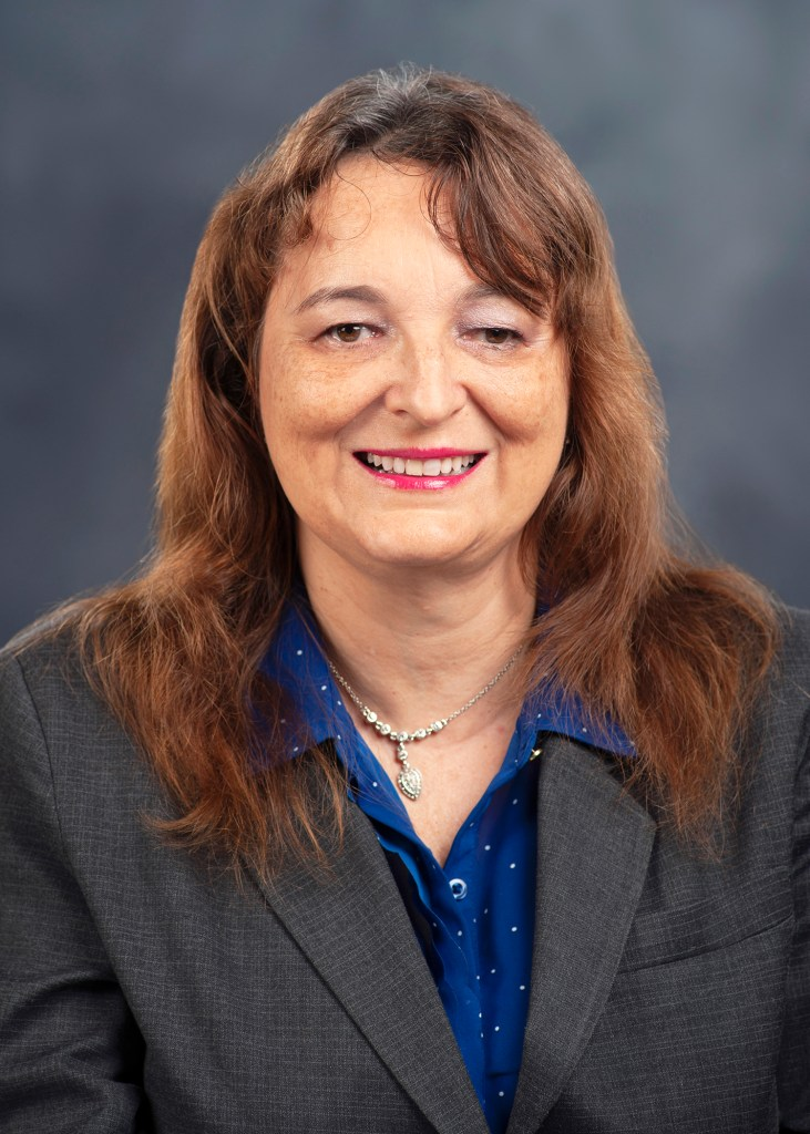 Professional headshot of Sylvia Stinson-Perez. She has Auburn hair and is wearing a blue shirt with a gray suit jacket.