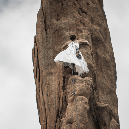 Photo of a woman scaling a mountain wearing a long white dress and rock climbing gear on her back and around her waist.