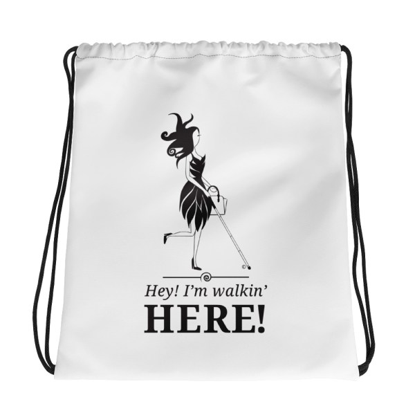 "White drawstring bag w/black ink. White mug w/black ink. The fashion icon Abby is front and center. Directly under Abby is the slogan ""Hey I'm Walkin' HERE!"""