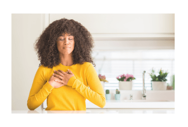 African American woman wearing yellow sweater in a kitchen smiling with closed eyes and her hands on her chest a graetful expression on her face.