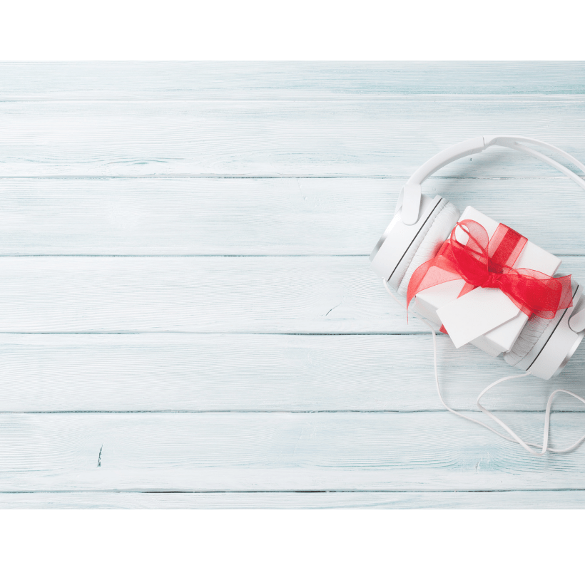 Self-care Sunday image is a Christmas music gift concept. Headphones and gift box on a wooden table.
