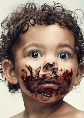 Adorable photo of a curly haired baby with chocolate smeared on her face.