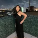 An evening outdoor glamour shot of Gabby standing with her hand on her hip in a black gown. Her long dark loosely curled tresses are flowing over her right shoulder and down her back.