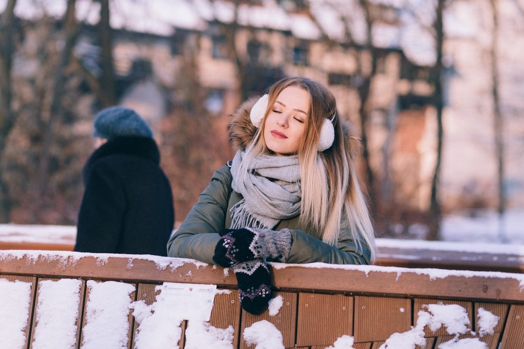 A snowy photo of a woman clad in earmuffs, scarf, coat and gloves stands with her arms propped on an outdoor wooden railing. In the background is a man and a building.