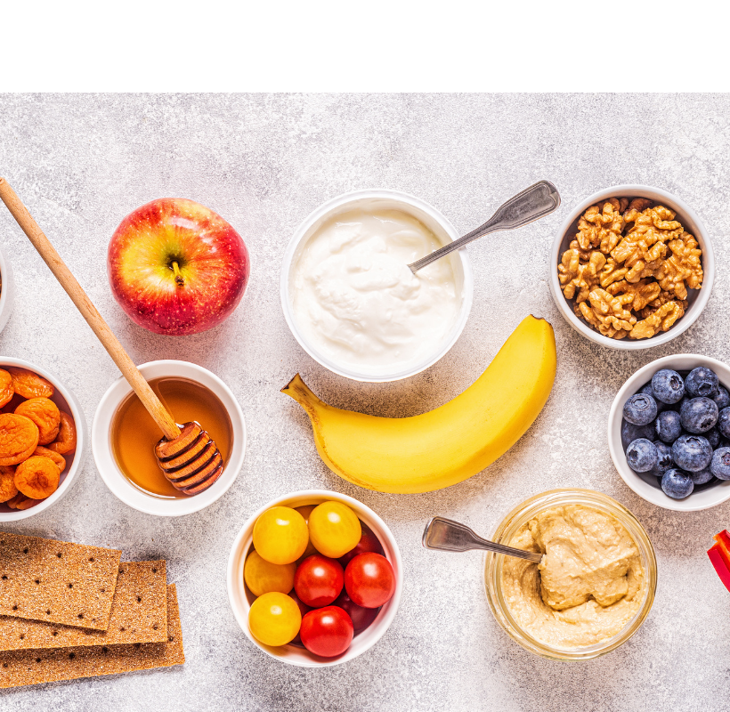 A top view of a healthy snack food background containing almonds, apple, apricot, banana, blueberries, honey, rice cakes, cherry tomatoes