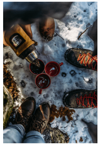 Coffee in the snowy outdoors. An aerial view of Stanley's classic 16-ounce thermos with a light brown leather coozie as it is poured into 3 camp mugs resting in the snow. Three pairs of hiking boots frame the photo.