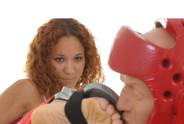 A martial artist with a fierce expression on her face is kicking her target.