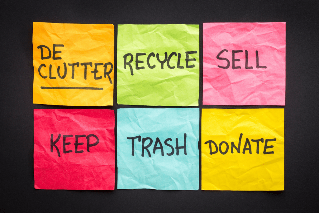 Handwriting on colored sticky notes against a black background. Each note has a word on it: Declutter, Recycle, Sell, Keep, Trash, Donate.
