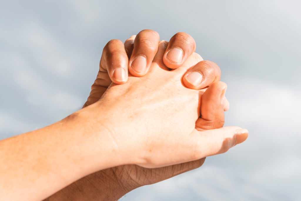 """""""Energetic Game of Follow the Leader"""" image of two hands clasped together with fingers intertwined."""