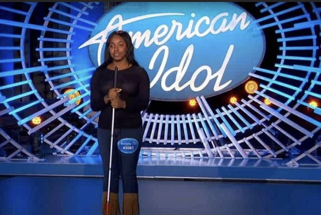 American Idol Audition photo of Shayy on stage with her white cane. She's wearing jeans, fringed boots with a black sweater, and a large American Idol logo is lit up behind her.
