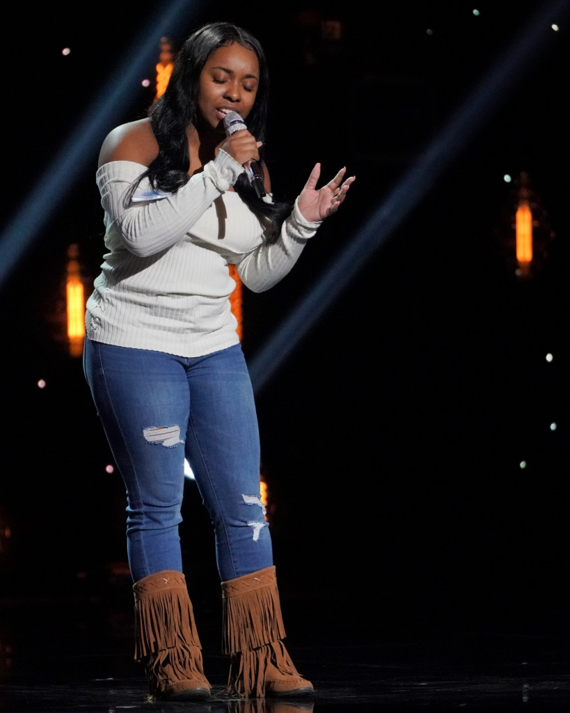 "AMERICAN IDOL - ""Hollywood Week"" - Coverage. (ABC/Eric McCandless) SHAYY is performing on stage wearing a white off-the-shoulder sweater with jeans, and brown fringed boots."