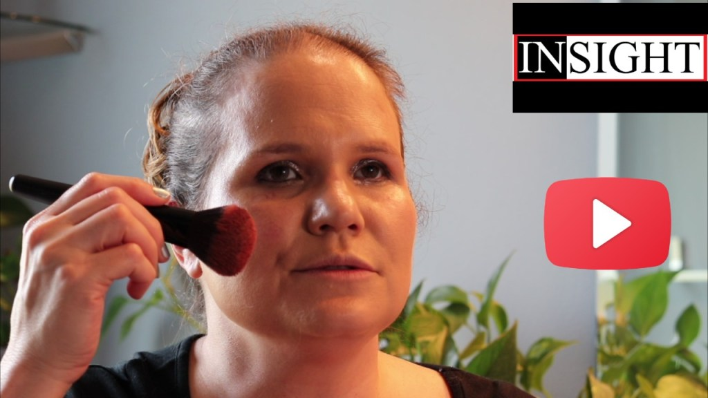 Insight4Blind on YouTube: A headshot of Jaz holding up a make-up brush to demonstrate how to evenly apply blush. Her face is smooth and clean with evenly applied foundation, light silver eye shadow, and eyeliner. In the top right corner of the image is the Insight banner and beneath it is the YouTube logo.