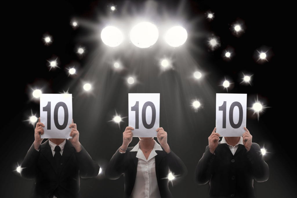 3 judges in a row each holding up a scorecard showing a perfect 10.