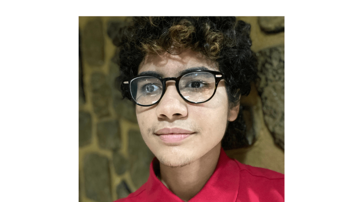 A frontal headshot of Liam who has dark curly hair and dark-framed eyeglasses.
