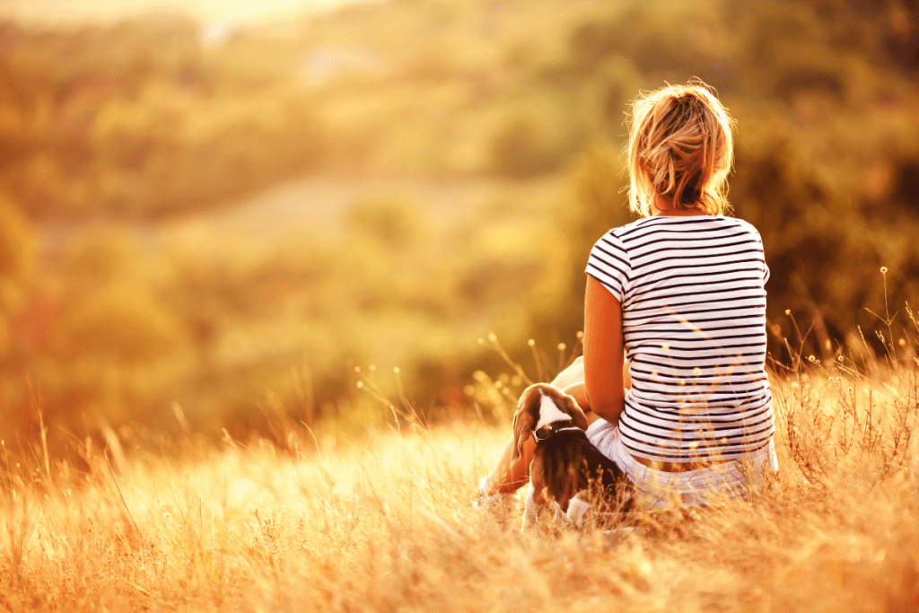 Woman with a beagle sitting in a field enjoying a beautiful summer day outside.