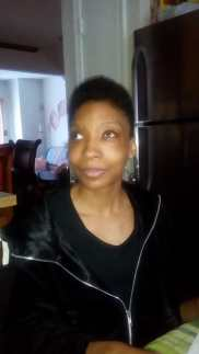 A headshot of Dana wearing a black scoop neck top under a black jacket. She has glowng caramel colored skin and short dark hair.