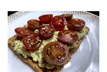 Egg salad on crispbread, topped with halved cherry tomatoes