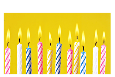 A close up of colorful birthday candles against a yellow background.