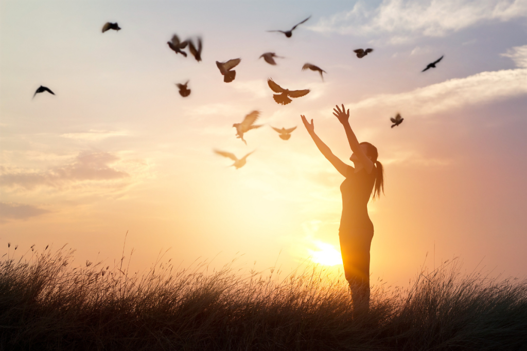 Forgiveness concept photo of birds flying at sunset and a woman with her arms raised as if letting go.