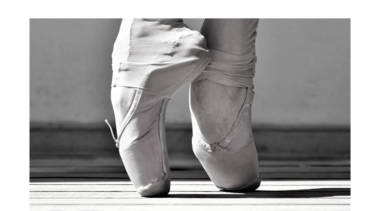 Black & white photo of ballerina slipper clad feet on pointe