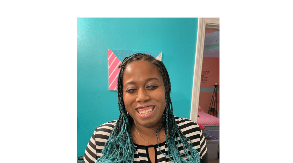 A headshot of Lily an attractive African American woman smiling broadly. Her hair is styled in long thin braids dyed a light blue on the ends. She is wearing a black & white striped top.
