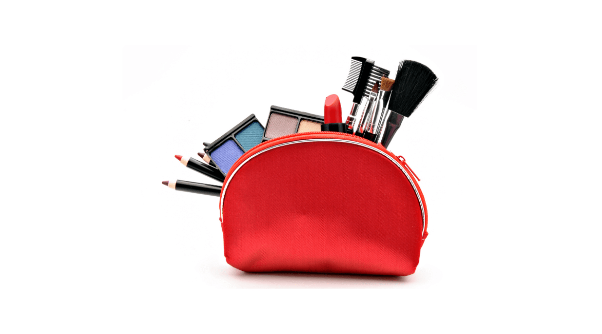 Assorted cosmetics and tools poking out of the top of a red makeup bag