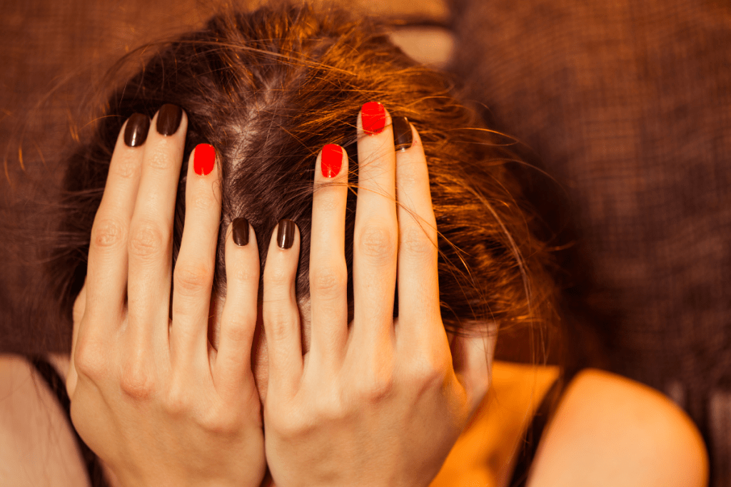 Young woman hiding her face in her palms.