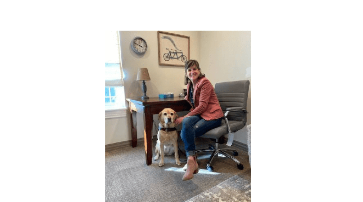 Becky Andrews is sitting at her desk with Georgie (her faithful guide dog) sitting on the floor by her side.