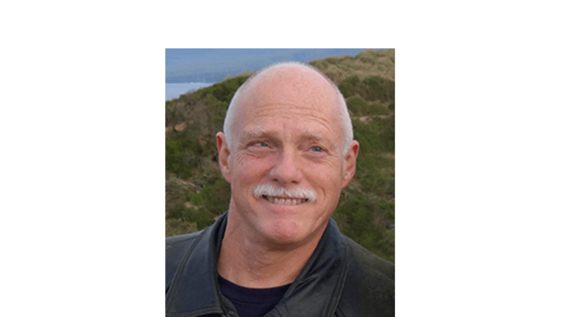 The header contains a photo of Ken a distinguished-looking white man smiling broadly. He has white hair and a white mustache and is wearing a gray jacket over a black tee.