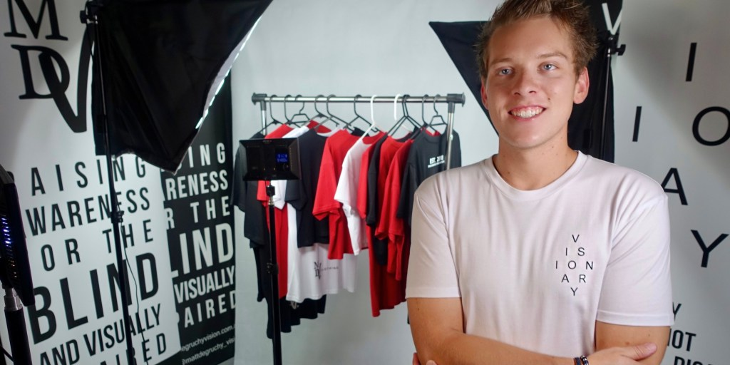 Matt is standing in front of a clothing rack containing his brand apparel.