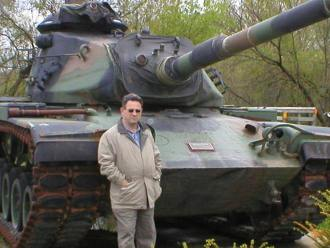 Tim Bolen in front of a WWII Sherman Tank parked as a War Memorial in a City park in Central Wisconsin.