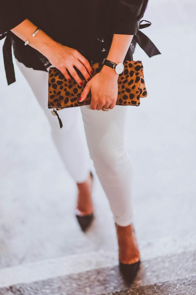 black off-the-shoulder cutout top, white distressed skinny jeans, janessa leone camellia white fedora, daniel wellington watch, clare v leopard foldover clutch, christian louboutin black patent pigalle pumps, le specs prince sunglasses
