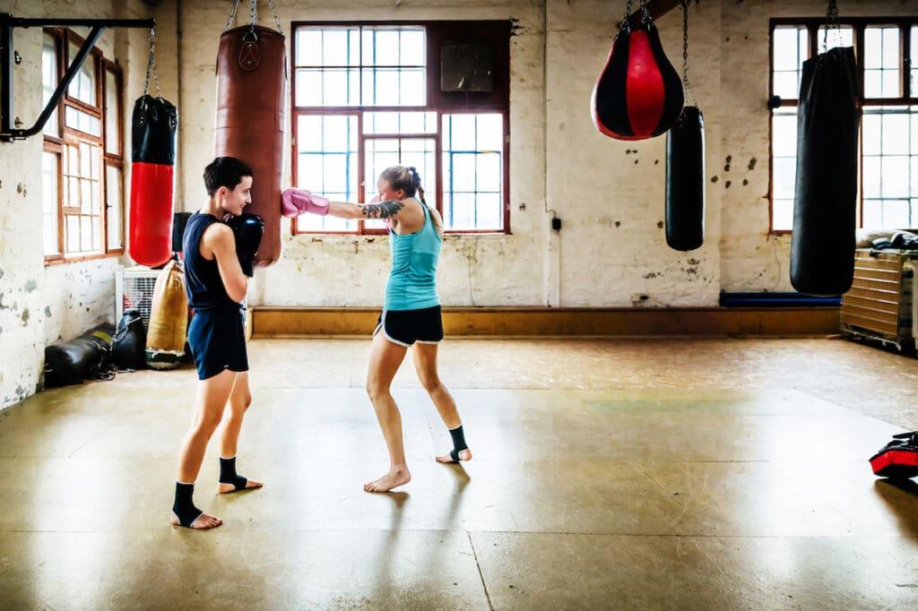 Female muay thai boxers training with sandbag in a gym.