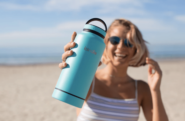 blonde woman holding up blue drink bottle on a beach