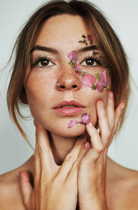 Woman with clear skin and flower petals on face. Photo by Joe Robles on Unsplash