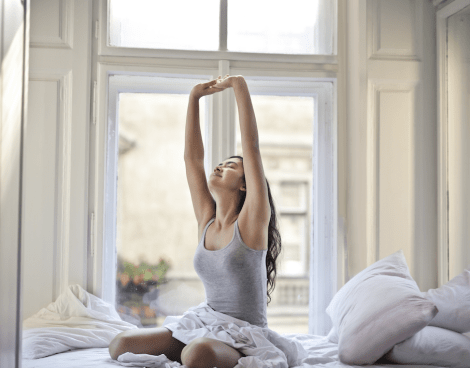 Girl stretching arms up in bed. Photo by bruce mars on Unsplash