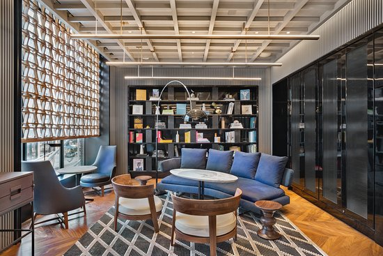 Designer room with squared ceilings, book shelf and coloured plush chairs