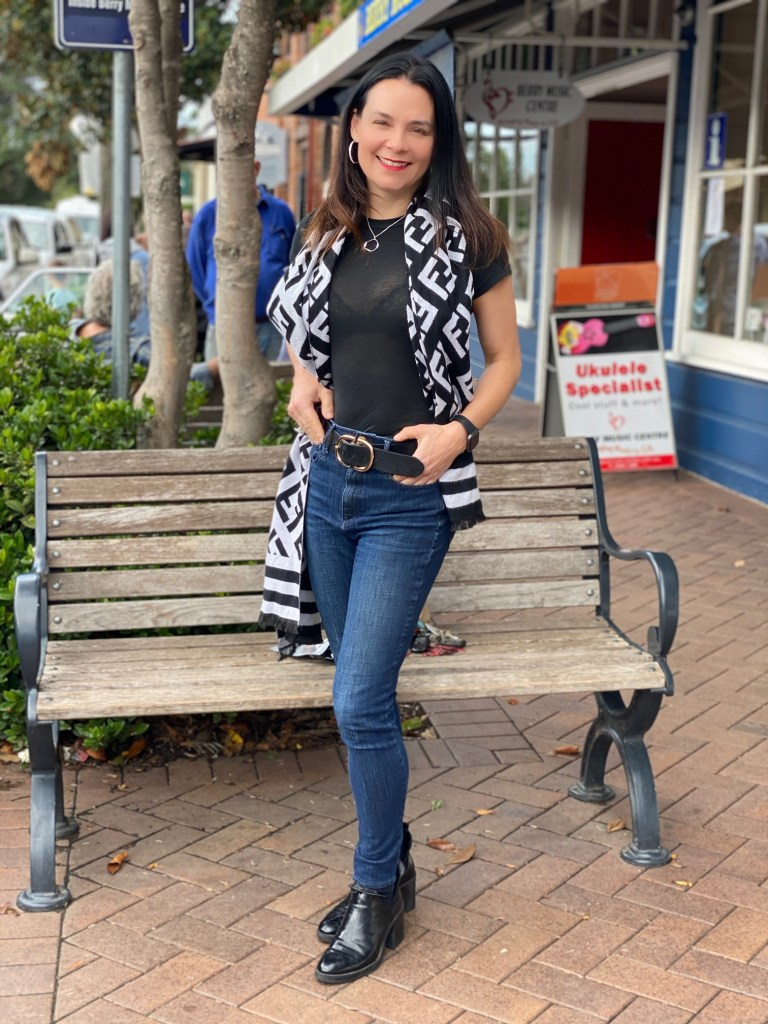 woman in black t-shirt, blue jeans and black and white scarf in Berry, NSW