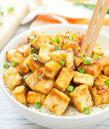 Crispy baked tofu and rice with chopsticks in white bowl
