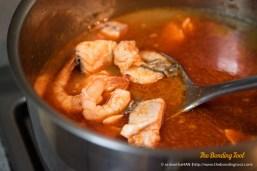 Tomyum salmon and prawn soup with straw mushrooms.