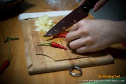 Mincing the garlic and chilli padi.
