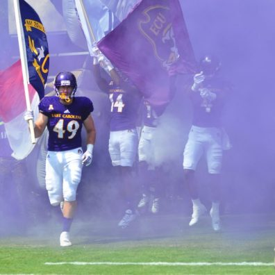 Senior Brian Hardy (49) carries the North Carolina flag into Dowdy-Ficklen Stadium. East Carolina is 2-0 on the 2016 season, and 2-0 against in-state opponents as well. (WA Myatt photo)