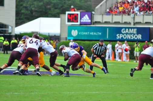 Junior inside linebacker Cannon Gibbs tackles Hokie running back Steven Peoples for a loss. (Photo by W.A. Myatt)