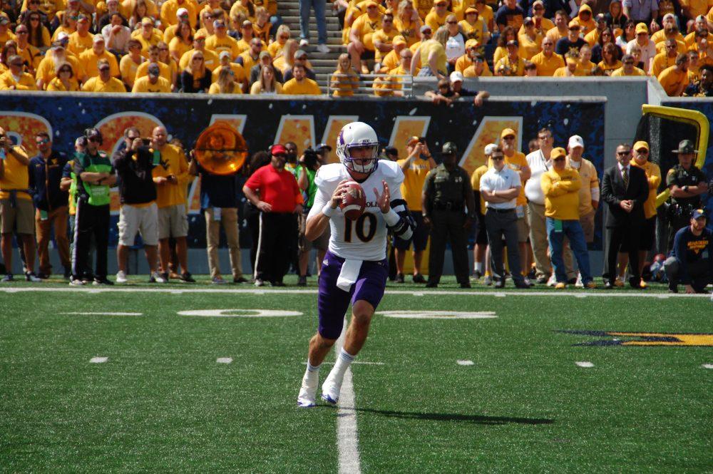 ECU quarterback Thomas Sirk sprints out before a crowd of 56,797 at West Virginia on Saturday. (Photo by Al Myatt)