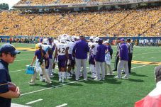 "The Pirate defense huddles up on Saturday before a ""Gold Rush"" crowd in Morgantown, WV. (Photo by Al Myatt)"
