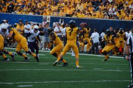 West Virginia quarterback Will Grier throws to receiver Gary Jennings Jr. (12) of the Mountaineers. (Photo by Al Myatt)