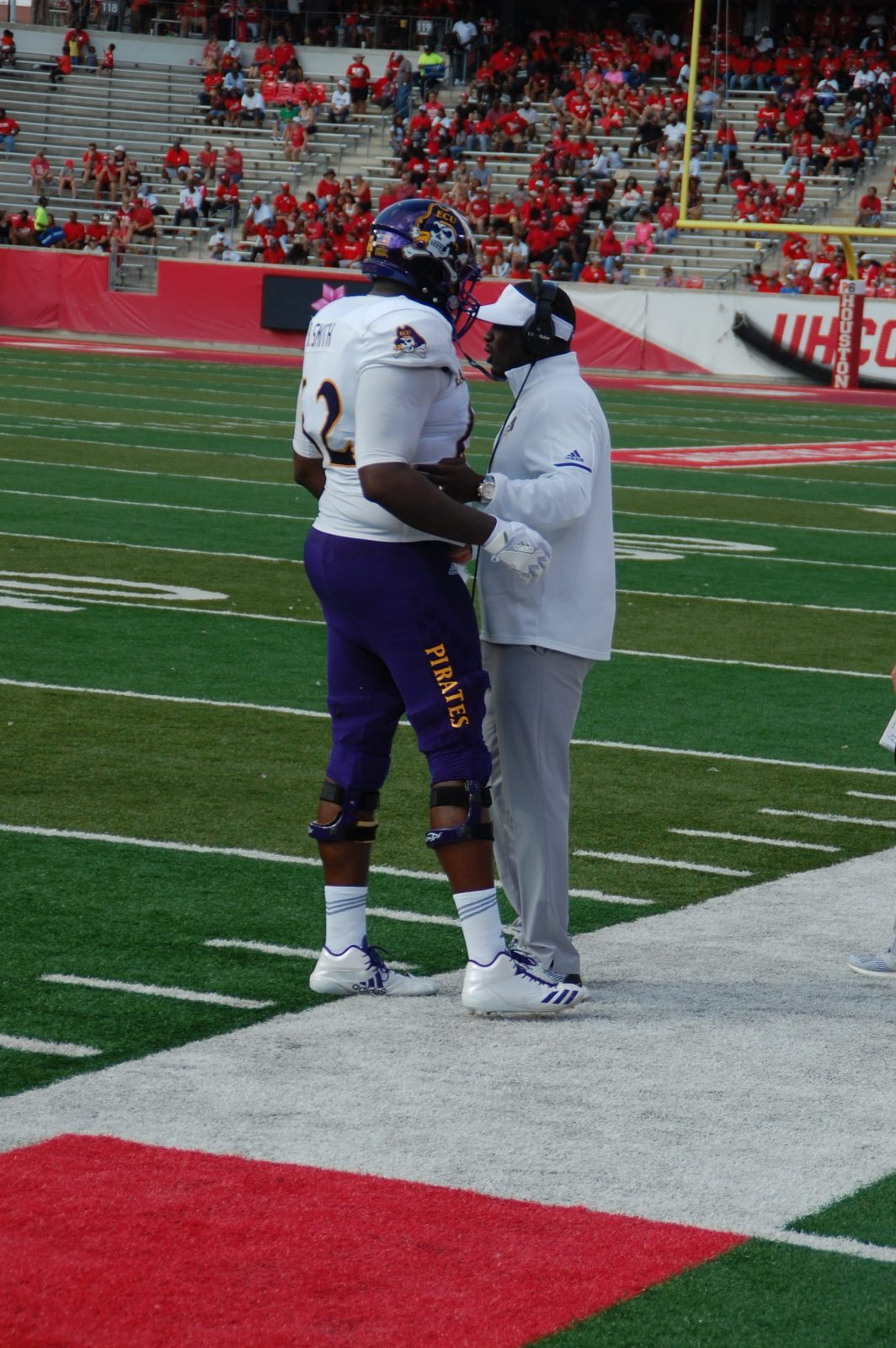 ECU coach Scottie Montgomery has a word with Brandon Smith as the offensive lineman comes off the field. (Photo by Al Myatt)
