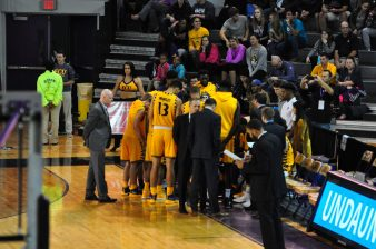 The Pirates huddle up during a timeout against UNC Wilmington. (Photo by Al Myatt)