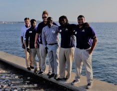 The East Carolina contingent beside Narragansett Bay before the clambake at the American Athletic Conference football kickoff on Monday evening. From left are acting chief officer of the athletic department Lee Workman, linebacker Bruce Bivens, offensive lineman Garrett McGhin, coach Scottie Montgomery, receiver Trevon Brown and defensive lineman Alex Turner. (Photo by Al Myatt)