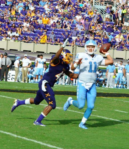 Pirates defender Devon Sutton pressures UNC quarterback Nathan Elliott into throwing the ball away. (Photo by Al Myatt)